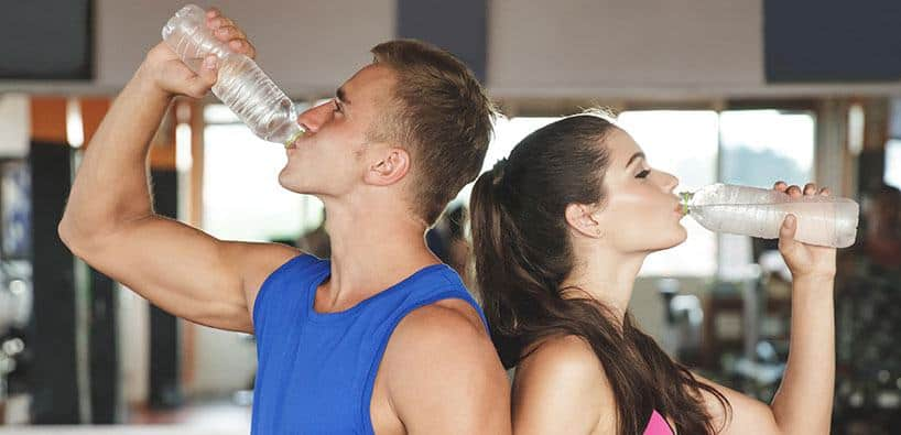 Man and Woman hydrating after workout