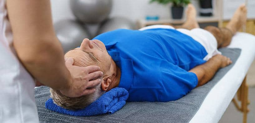 A massage therapist doing a massage to an elderly man at Green Apple